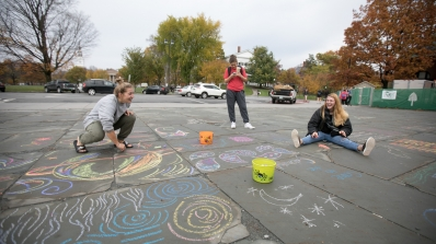 Students draw with sidewalk chalk.
