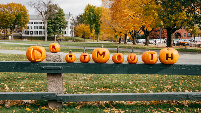 "Carved pumpkins spelling out ""Dartmouth"" sit on a fence."