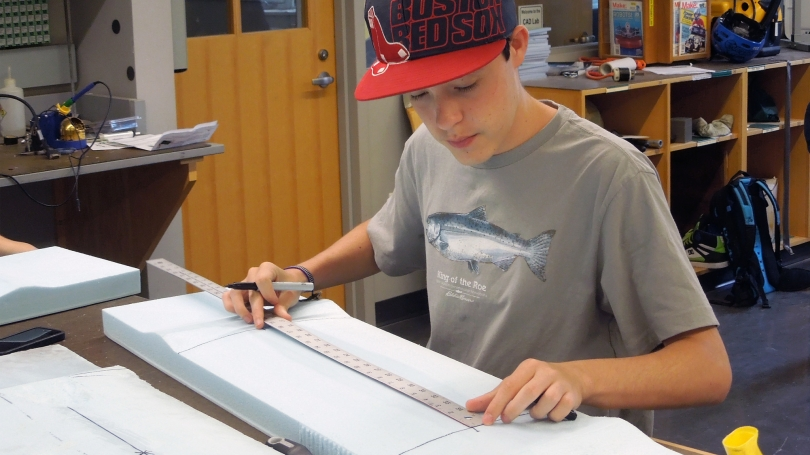 A student uses a measuring stick while working on a project.