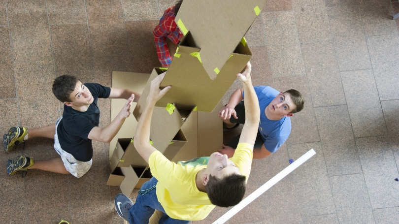 Students build a cardboard tower.