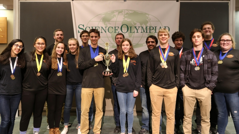 A team poses with Dean Kill and their Olympiad medals.