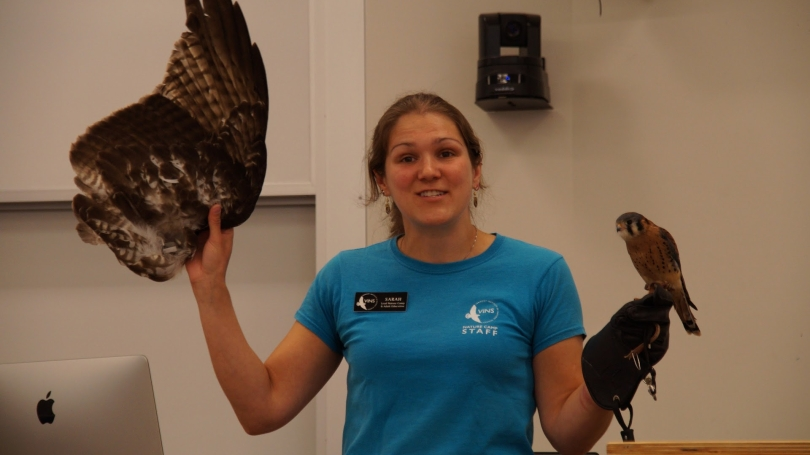 A woman holds a bird.